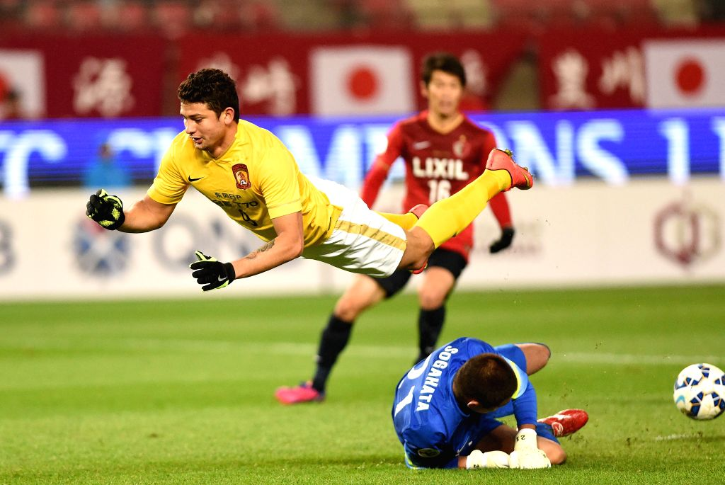 Elkeson (L) of China's Guangzhou Evergrande is tackled by Hitoshi Sogahata of Japan's Kashima Antlers during their group H match at the 2015 AFC Champions League in ...