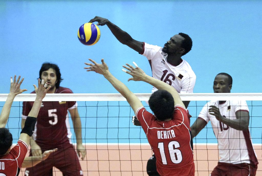 Ibrahim Ibrahim (top C) of Qatar spikes the ball during the match against Japan at the 18th Asian Men's Volleyball Championship at Azadi Stadium in Tehran, Iran, on ...