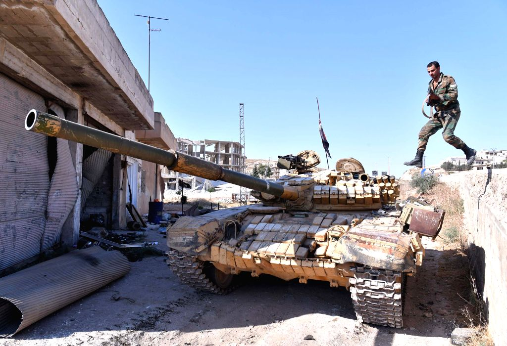 IDLIB (SYRIA), Aug. 24, 2019 A Syrian soldier jumps onto a tank in the town of Khan Shaykhun in the southern countryside of Idlib province, Syria, on Aug. 24, 2019. The Syrian army on ...