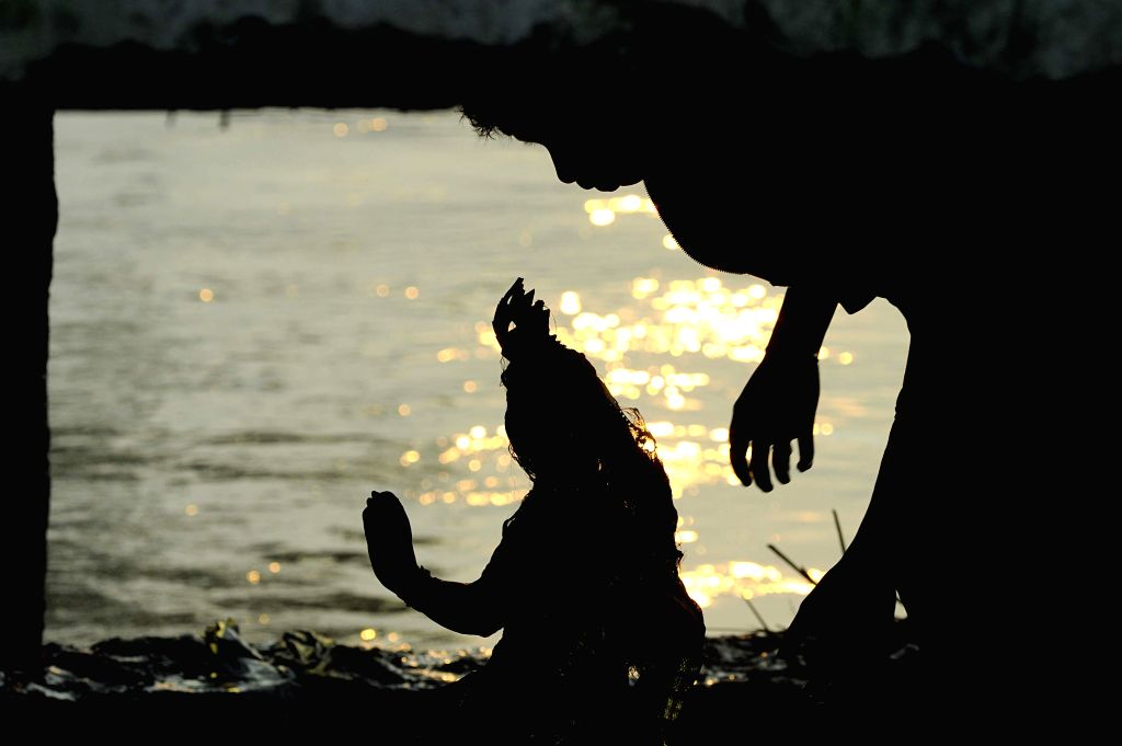 Idol of goddess Lakshmi being immersed after Lakshmi Puja on the banks of Hoogly river in Kolkata on Oct.19, 2013. (Photo: IANS)
