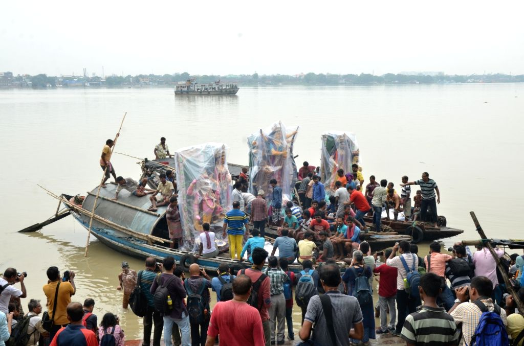 Idols of Goddess Durga from a workshop in Kumartoli being transported on a boat through the waters of Ganga river to a pandal ahead of Durga Puja celebrations, in Kolkata on Sep 27, 2019.