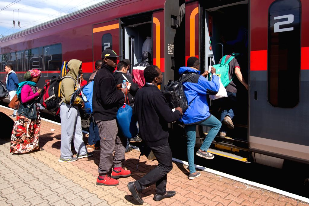 Illegal migrants traveling to Germany get on a train bound for Munich at a railway station near Austrian border in Hegyeshalom, Hungaryr. (Xinhua/Attila Volgyi/IANS)