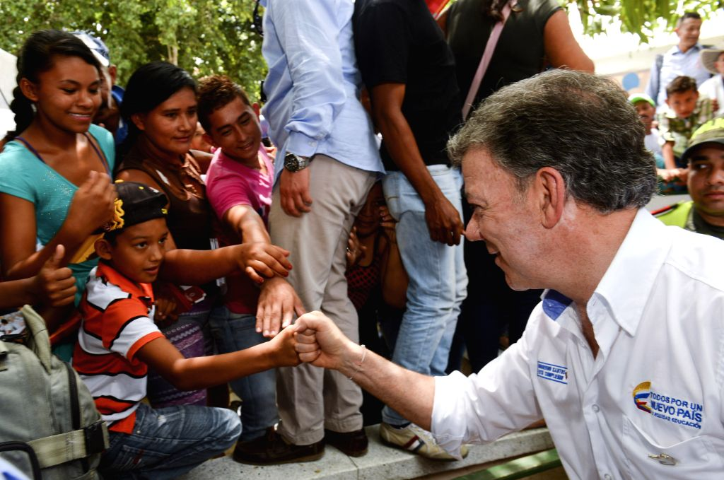 Image provided by Colombia's Presidency shows the Colombian President Juan Manuel Santos (R) greeting a boy during his tour on the streets in the locality of Oveja, ...