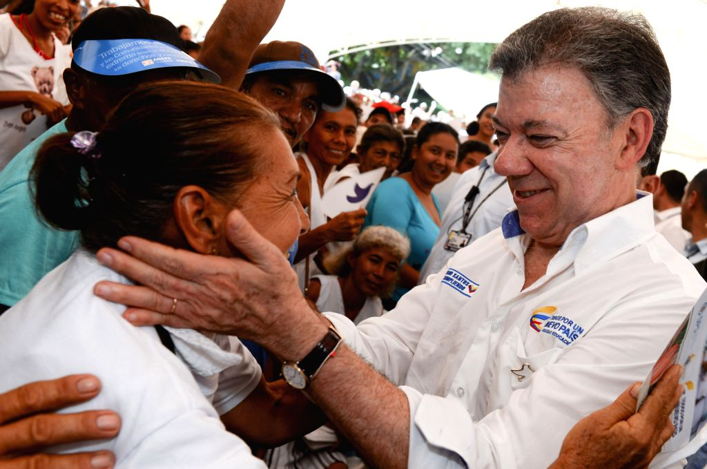 Image provided by Colombia's Presidency shows the Colombian President Juan Manuel Santos (R) greeting a woman during an event in the locality of Oveja, Sucre, ...