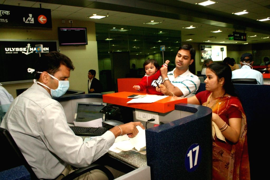 Immigration officer on duty with medical mask to protect him self from swine flu, at IGI Airport,in New Delhi on Thursday.