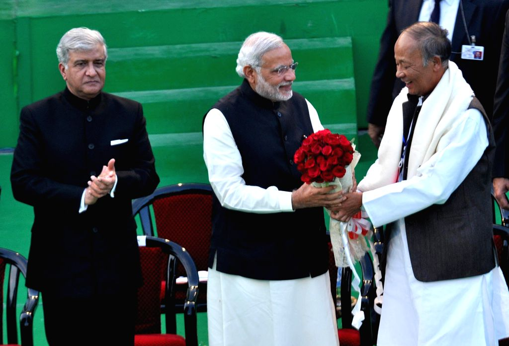 Manipur Chief Minister Okram Ibobi Singh presents a bunch of red roses to Prime Minister Narendra Modi during his visit to Imphal on Nov 30, 2014. - Okram Ibobi Singh and Narendra Modi