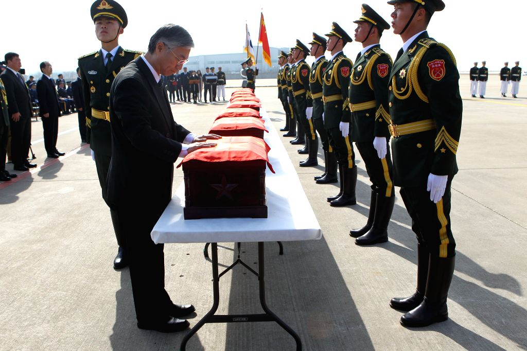 Chinese Ambassador to South Korea Qiu Guohong covers with a Chinese national flag a coffin containing remains of a soldier of the Chinese People's Volunteers (CPV) ...