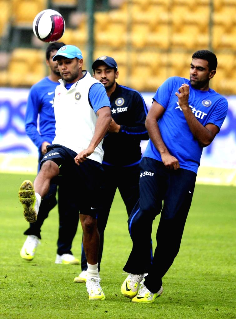 India cricketers Stuart Binny and R Ashwin warm up on the ground as rain delay the start of the 4th day of the second test match between India and South Africa at M Chinnaswamy Stadium in ...