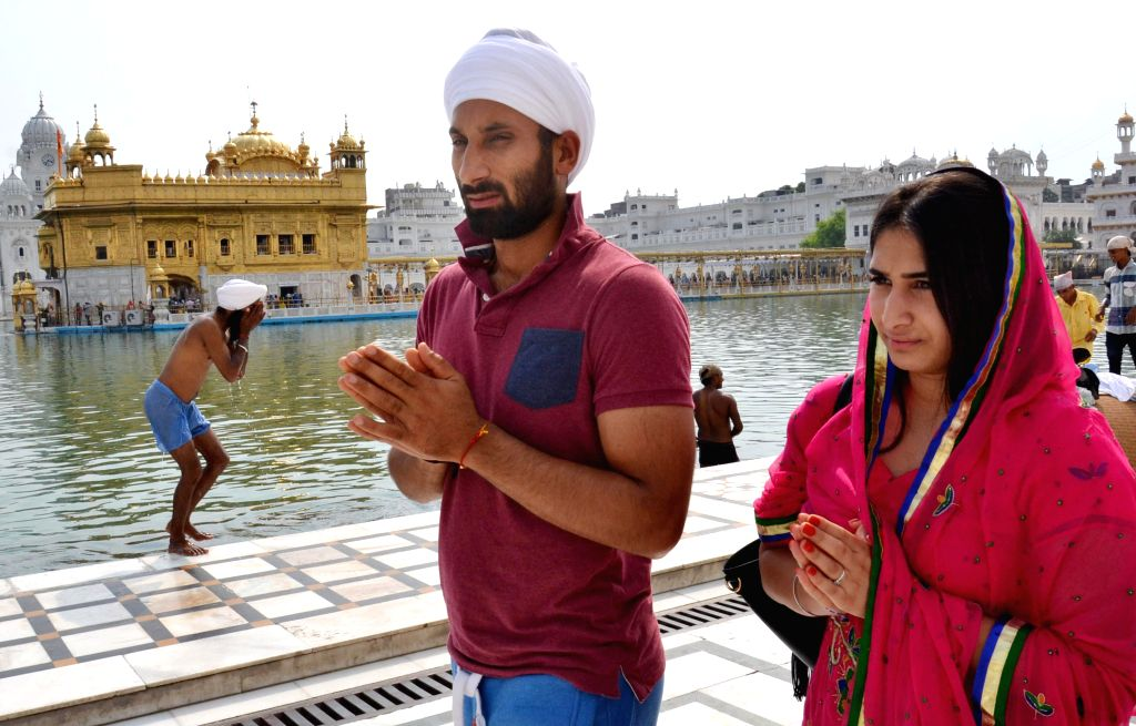 India hockey captain Sardar Singh and his fiancee England junior hockey player Ashpal Bhogal during their visit to the Golden Temple in Amritsar on Aug 11, 2014.