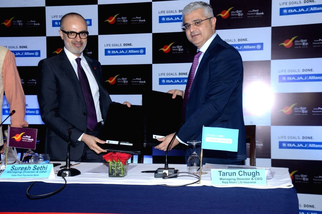 India Post Payments Bank MD and CEO Suresh Sethi and Bajaj Allianz Life MD and CEO Tarun Chugh at the signing ceremony of Corporate Agency Agreement between IPPB and Bajaj Allianz Life in ...