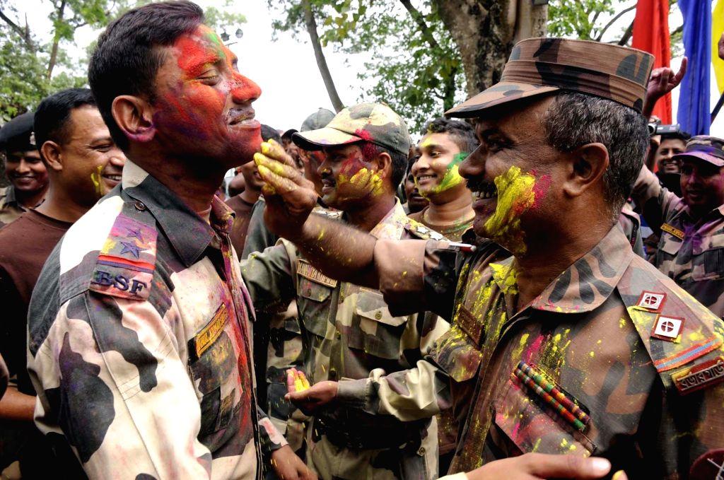 India's Border Security Force (BSF) and Border Guards Bangladesh (BGB) play Holi at Akhaura integrated checkpost in Tripura on March 12, 2017.