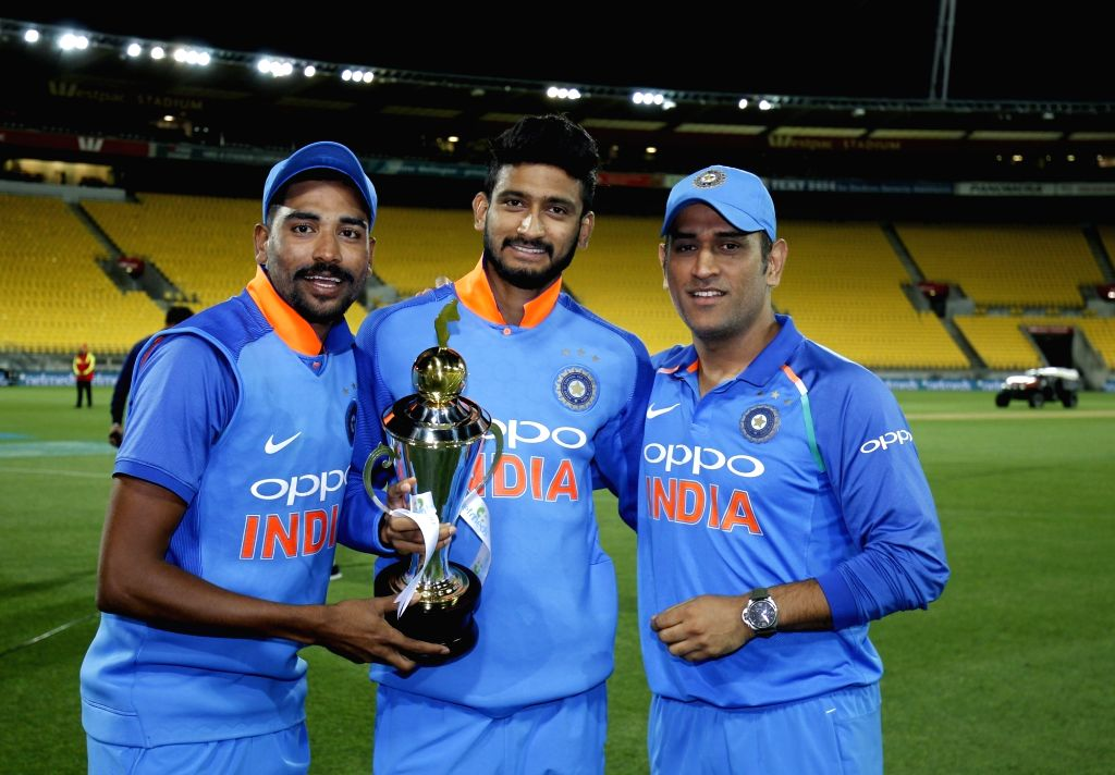 India's Mohammed Siraj, Khaleel Ahmed and MS Dhoni pose with the trophy after a 35-run victory against New Zealand in the fifth and final One Day International (ODI) match, thereby ... - MS Dhoni