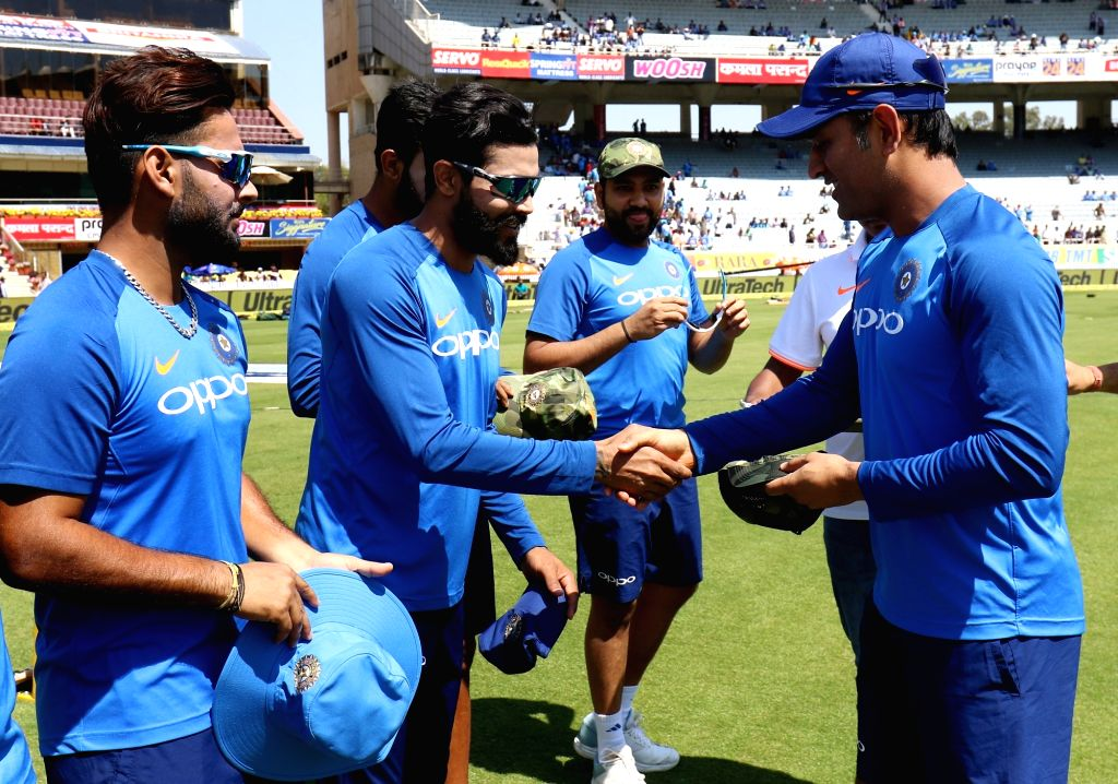 India's MS Dhoni presents a camouflage cap to teammates ahead of  the third ODI match against Australia at JSCA International Stadium Complex in Ranchi on March 8, 2019. 'Men in Blue' will be ... - MS Dhoni