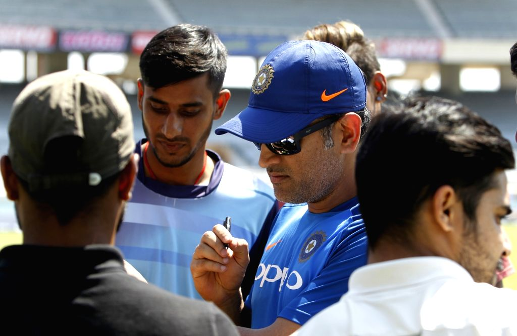 India's MS Dhoni sings an autograph for his fans during a practice session ahead of the third ODI match against Australia, in Ranchi, on March 7, 2019. - MS Dhoni