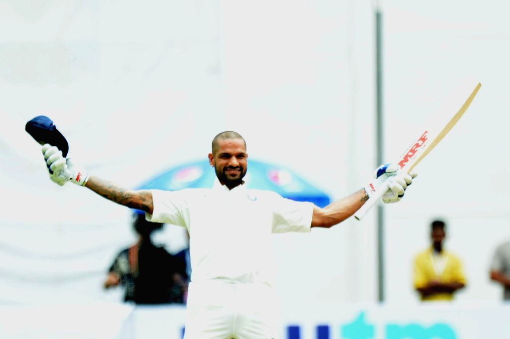 India's Shikhar Dhawan celebrates his century on Day 1 of the one-off test match between India and Afghanistan at M. Chinnaswamy Stadium, in Bengaluru on June 14, 2018. - Shikhar Dhawan