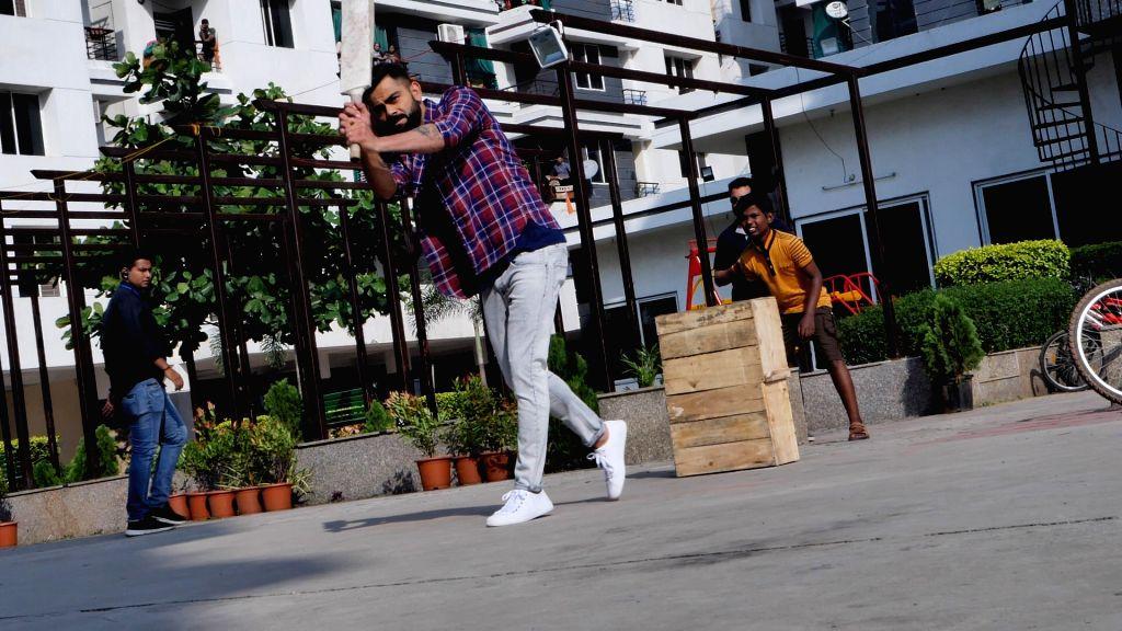 India skipper Virat Kohli spotted playing gully cricket with children during a shoot at Bicholi Mardana area, in Indore on Nov 13, 2019. - Virat Kohli
