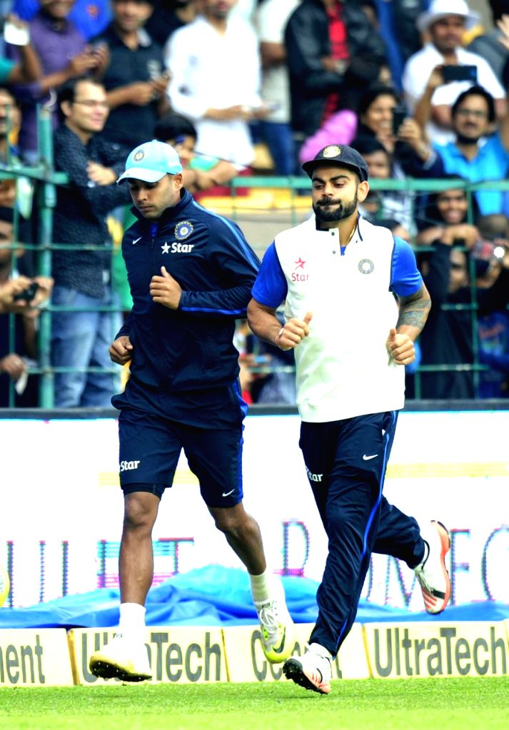 India skipper Virat Kohli with teammate Stuart Binny warm up on the ground as rain delay the start of the 2nd day of the second test match between India and South Africa at M Chinnaswamy ... - Virat Kohli
