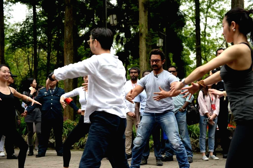 Indian actor Aamir Khan, left, takes part in a wrestling match with a local during his visit to Chengdu city in southwest China's Sichuan province, 20 April 2017. - Aamir Khan