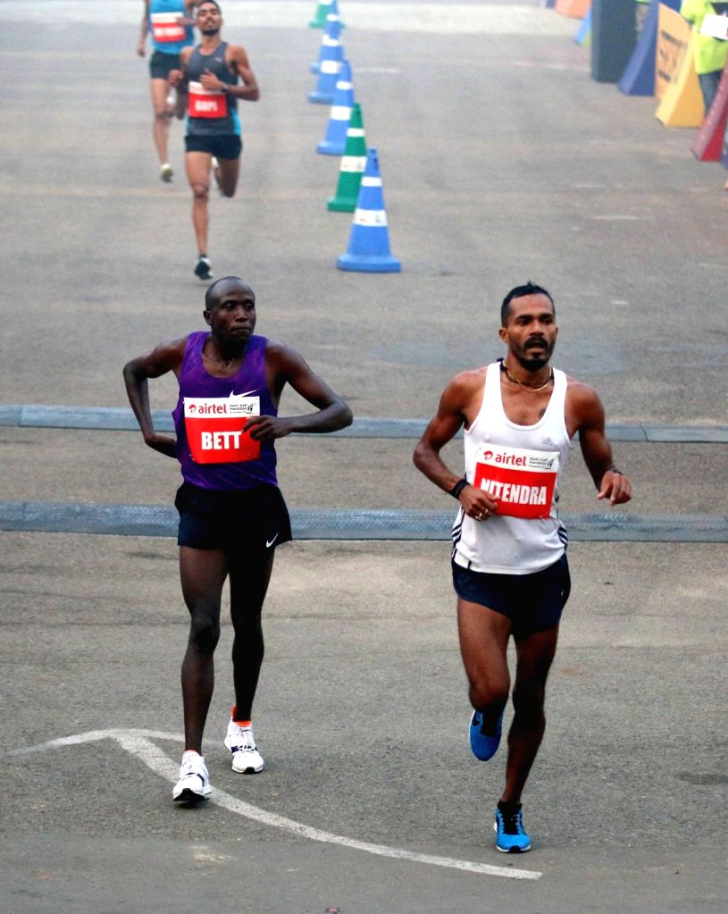 Indian athlete Nitendra Singh Rawat (R) after the finish of Indian Elite Men event at the Airtel Delhi Half Marathon, on Nov 29, 2015. - Nitendra Singh Rawat