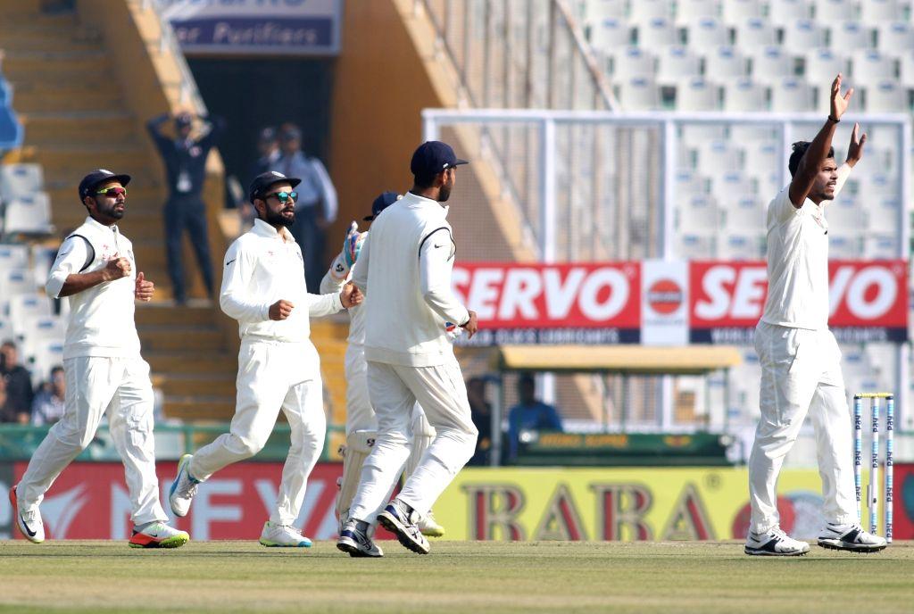Indian captain Virat Kohli and bowler Umesh Yadav celebrates the dismissal of England's Haseeb Hameed on the first day of their third cricket test match in Mohali on Nov. 26,  2016. - Virat Kohli and Umesh Yadav