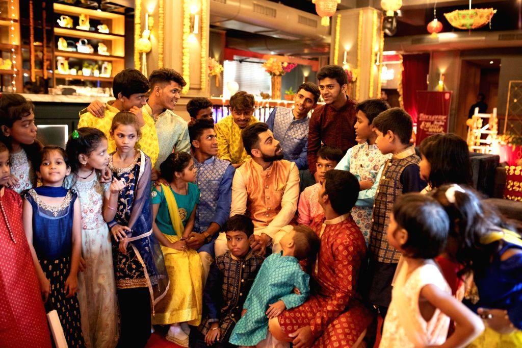 Indian cricket captain Virat Kohli celebrates Diwali with children in Mumbai's Dharavi. - Virat Kohli
