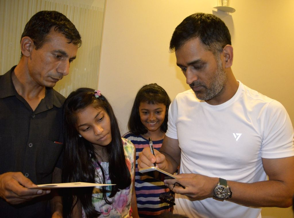 Indian cricketer MS Dhoni gives autographs to children during a promotional programme in in Gurugram on May 11, 2017. - MS Dhoni