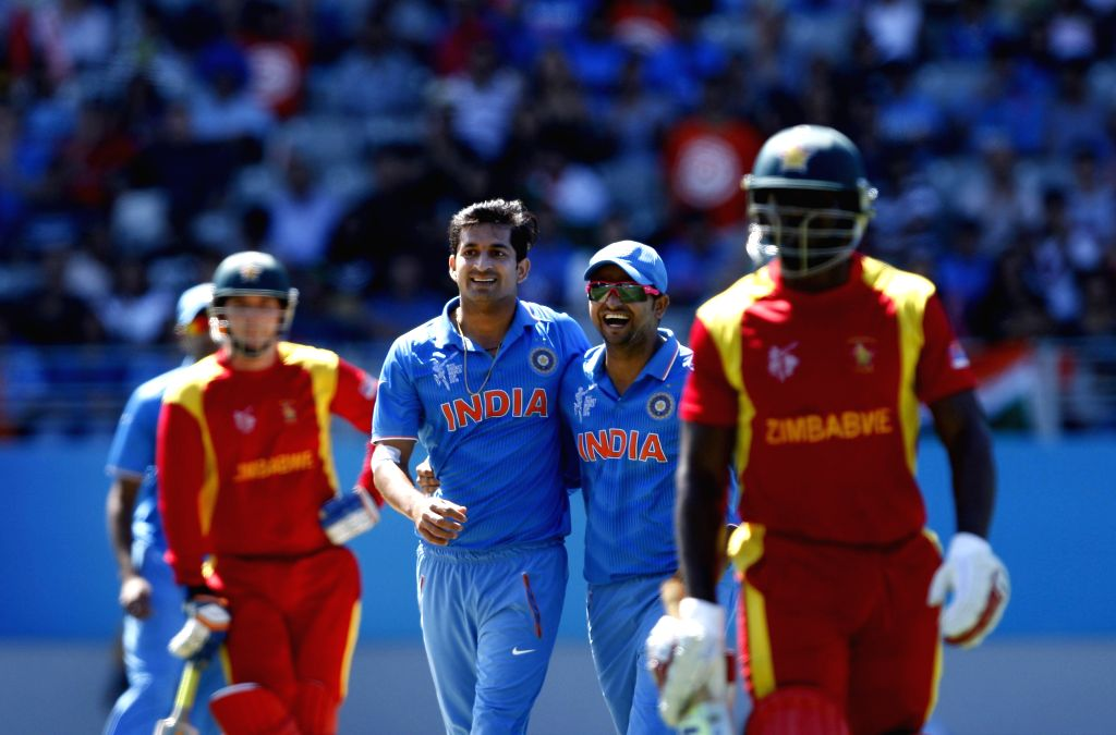 Indian cricketers Mohit Sharma and Suresh Raina celebrate fall of a wicket during an ICC World Cup 2015 match between India and Zimbabwe at the Eden Park in Auckland, New Zealand on March 14, 2015. - Mohit Sharma