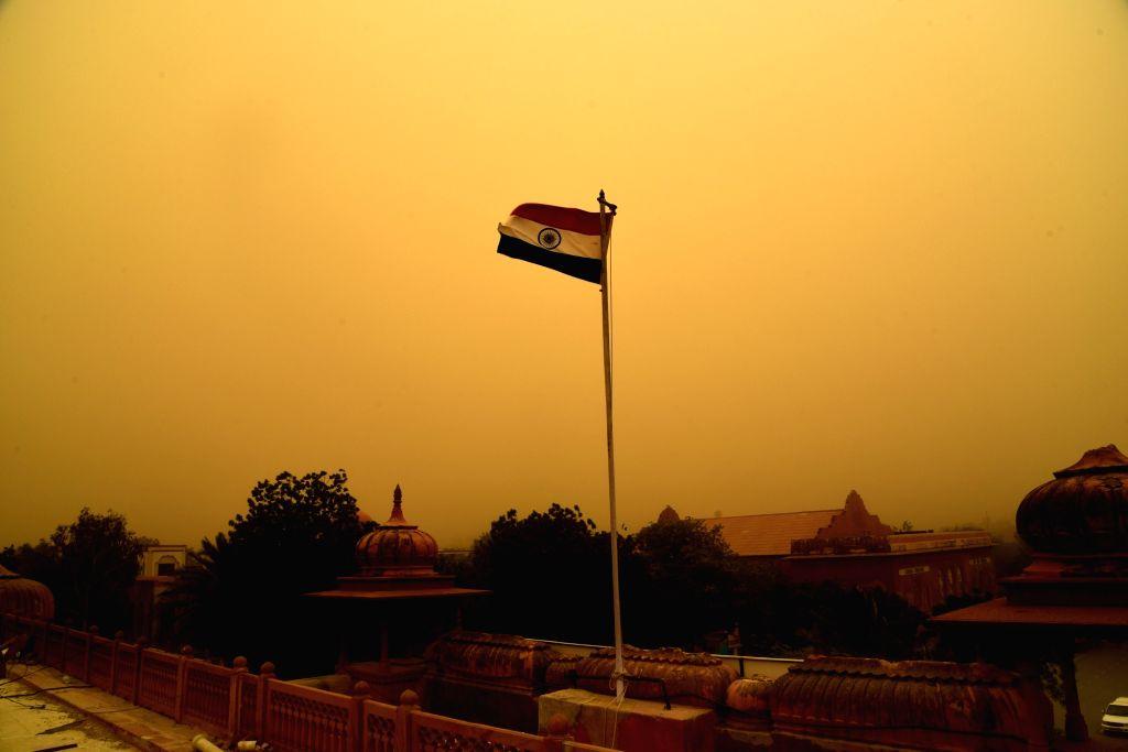 Indian flag flutters during a dust storm in Bikaner on June 14, 2018.
