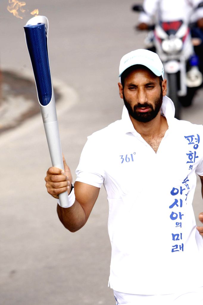 Indian Hockey team Captain Sardar Singh and Gurwinder Singh Chandi running with the torch of 17th Asian Games Incheon 2014, Korea at New Delhi on Aug. 9, 2014. - Sardar Singh and Gurwinder Singh Chandi