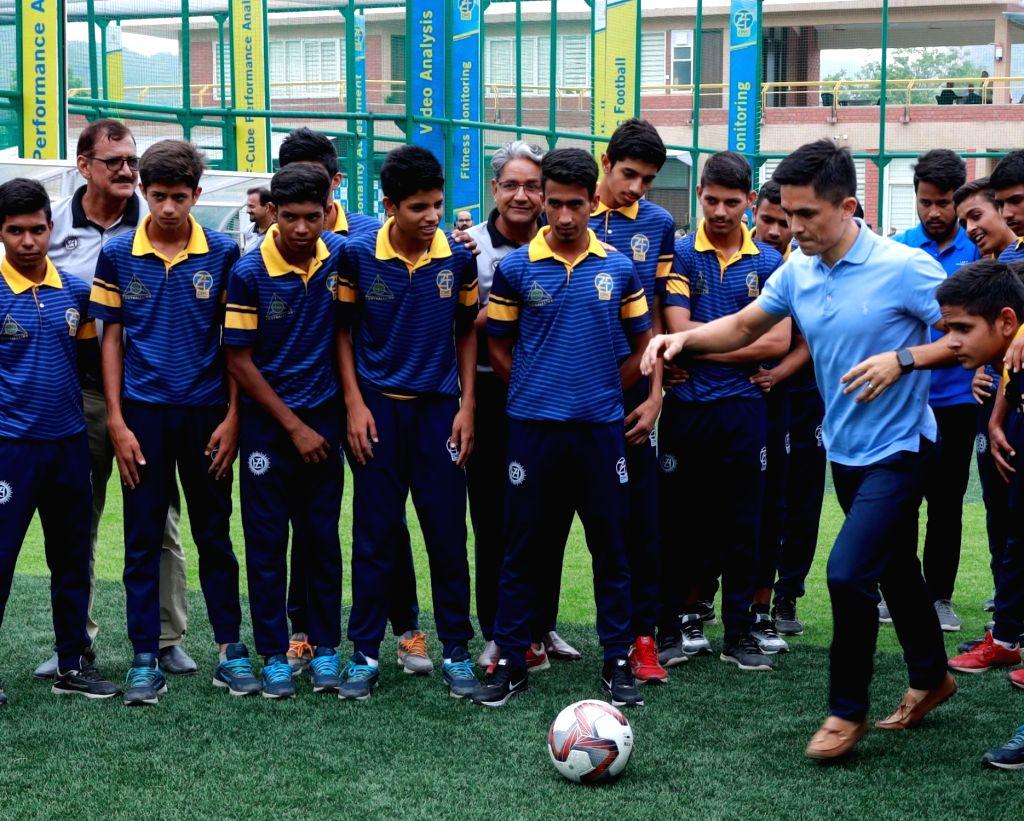 Indian National Football Team Captain Sunil Chhetri teaches Panenka kick to young footballers during his visit to the Zinc Football Academy at Zawar in Rajasthan's Udaipur, on July 27, 2019. - Sunil Chhetri