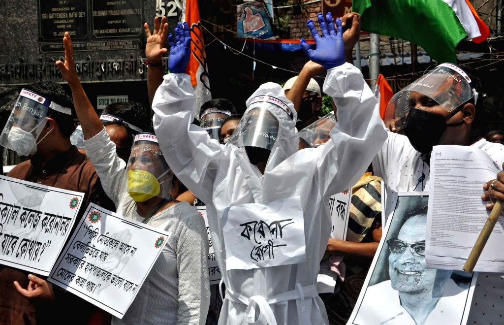 Indian National Trade Union Congress (INTUC) activists wearing Personal Protective Equipment (PPE) suits, masks and face shields stage a demonstration against the medical system of West ...