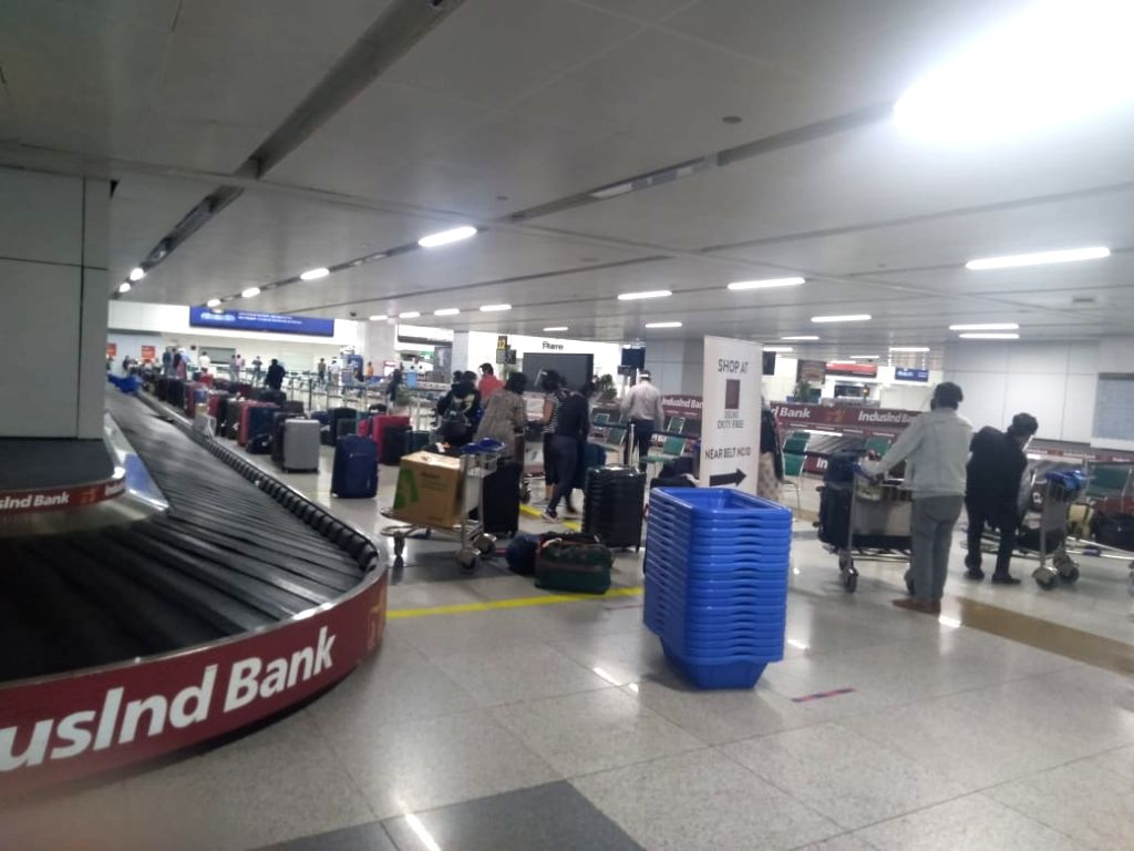 Indian nationals stranded abroad arrive from Signapore waiting to be screened before being take into quarantine facilities at Indira Gandhi International Airport in New Delhi on May 8, ...