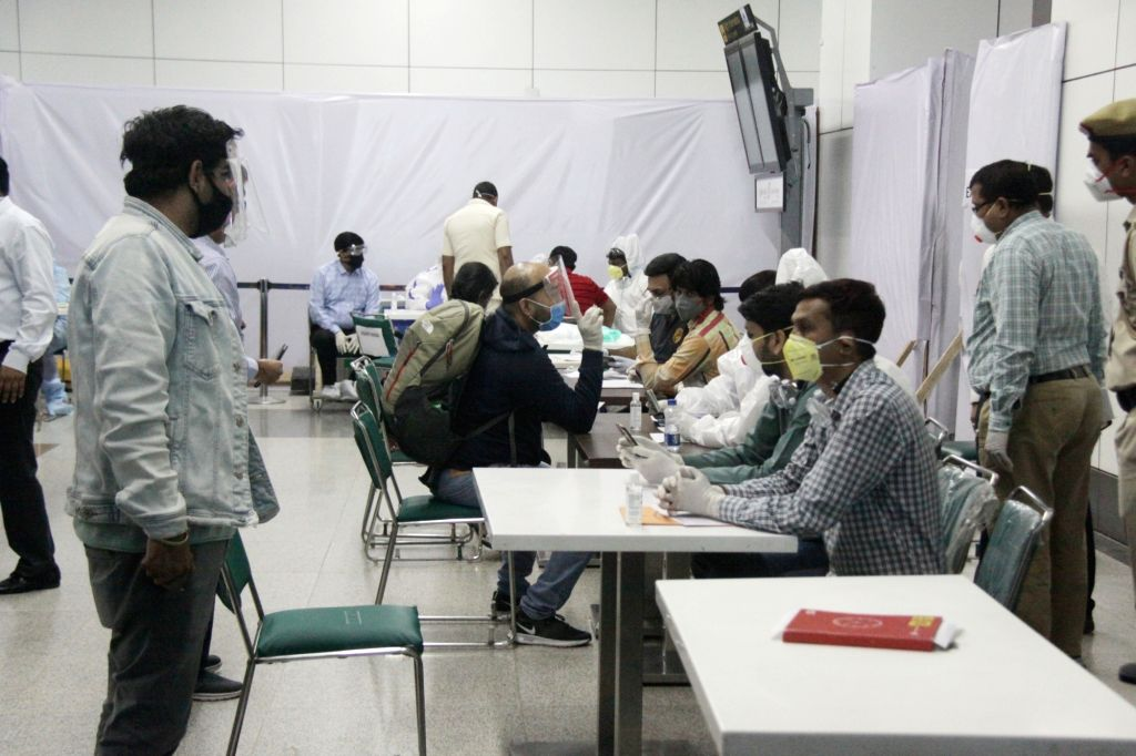 Indian nationals stranded abroad arrive from Signapore being screened for COVID-19 as they halt at Indira Gandhi International Airport in New Delhi on May 8, 2020.