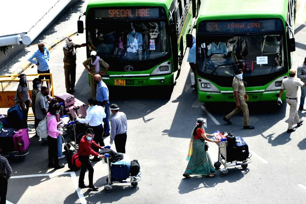 Indian nationals stranded abroad arrive from Singapore boards DTC buses as they are being taken away into quarantine facilities at Indira Gandhi International Airport in New Delhi on May ...