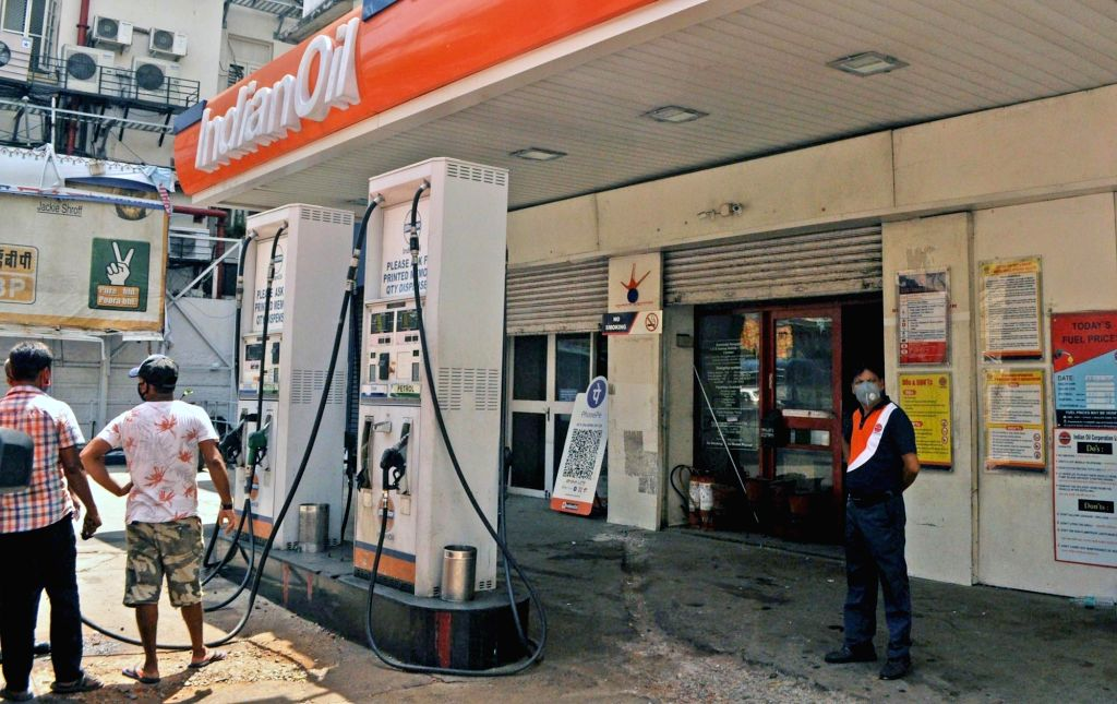 Indian Oil staff attend customers at a petrol pump in Kolkata on June 25, 2020. Transport fuel diesel prices continued its roll on Thursday, surpassing Rs 80 per litre mark in Delhi with oil ...