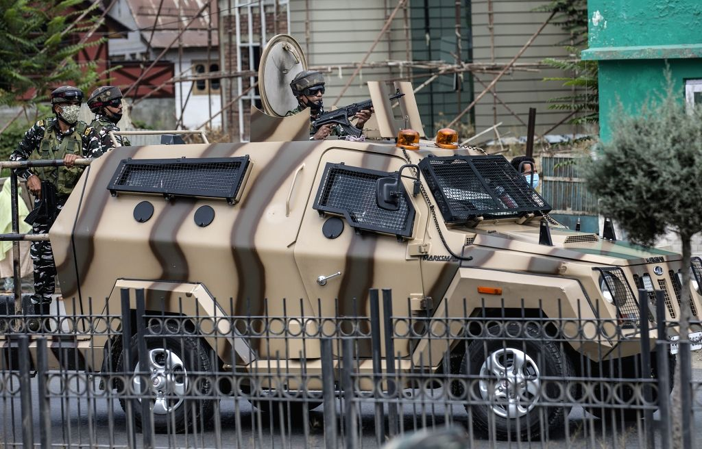 Indian paramilitary troopers stand guard on an armored vehicle at the site of a militants' attack on policemen in Srinagar city, the summer capital of ...
