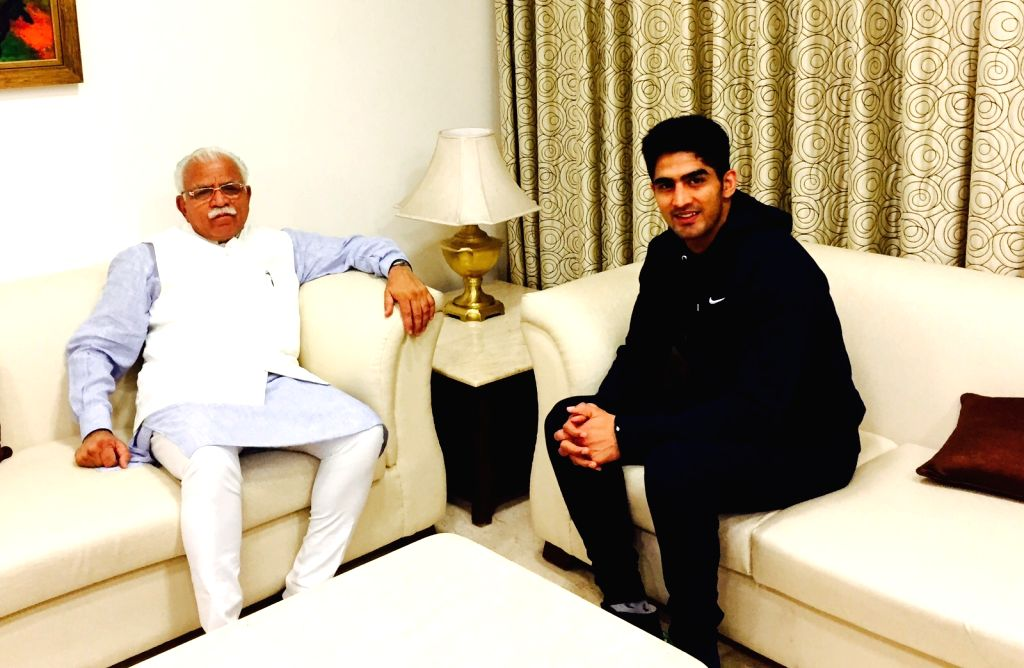 Indian Professional Boxer Vijender Singh during a meeting with Haryana Chief Minister Manohar Lal Khattar in New Delhi, on Nov 16, 2015. - Manohar Lal Khattar