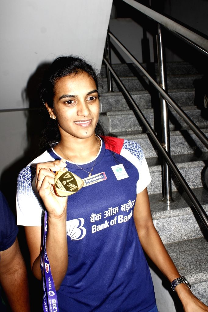 Indian shuttler P. V. Sindhu, who became the first Indian shuttler to win gold at the BWF World Championships pose with her medal at Gopichand Badminton Academy in Hyderabad on Aug 27, ...