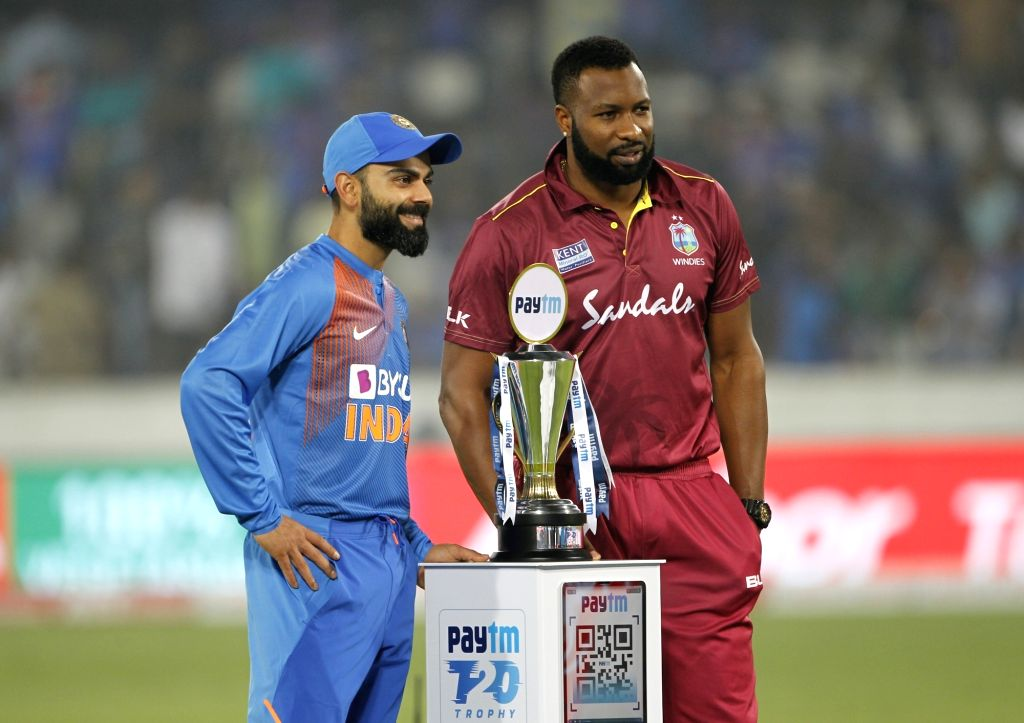 Indian skipper Virat Kohli and West Indies captain Kieron Pollard pose with the Trophy ahead of the first T20I match between India and the West Indies at the Rajiv Gandhi International ... - Kieron Pollard and Virat Kohli