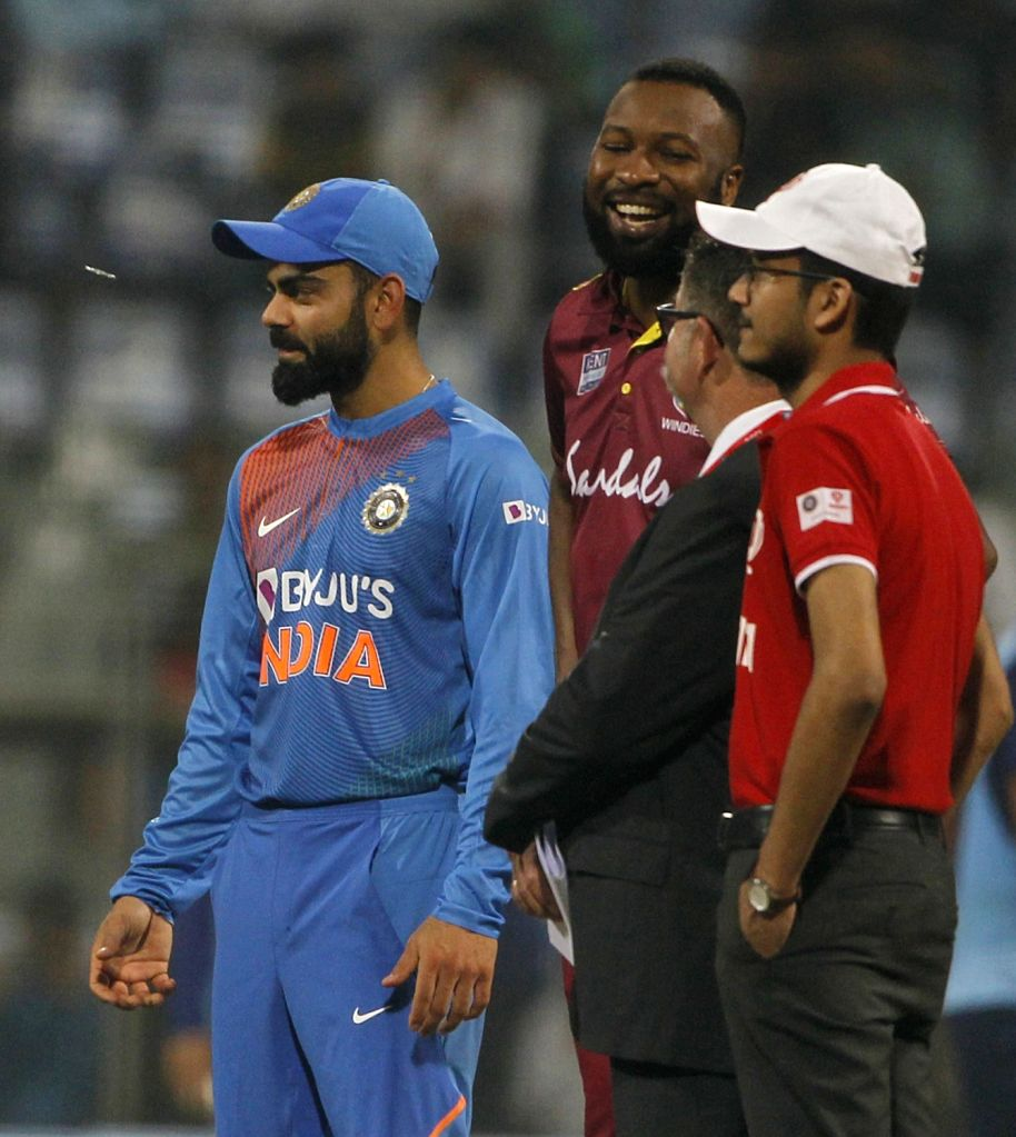 Indian skipper Virat Kohli and West Indies captain Kieron Pollard during the toss ahead of the third T20I match between India and West Indies at the Wankhede Stadium in Mumbai on Dec 11, 2019. - Kieron Pollard and Virat Kohli