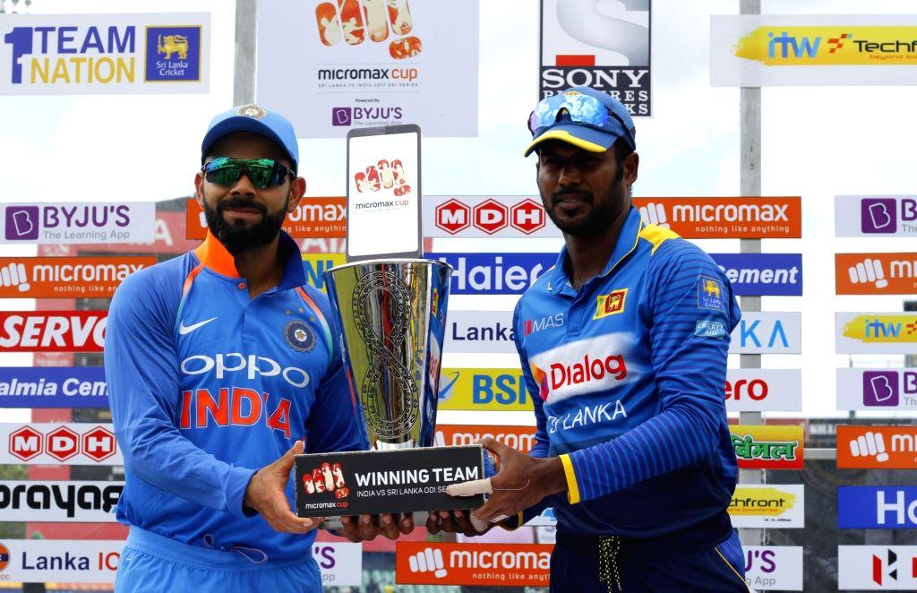 Indian skipper Virat Kohli (R) and Sri Lankan skipper Upul Tharanga (L) pose with the trophy ahead of the first ODI International cricket match between India and Sri Lanka at Rangiri ... - Virat Kohli