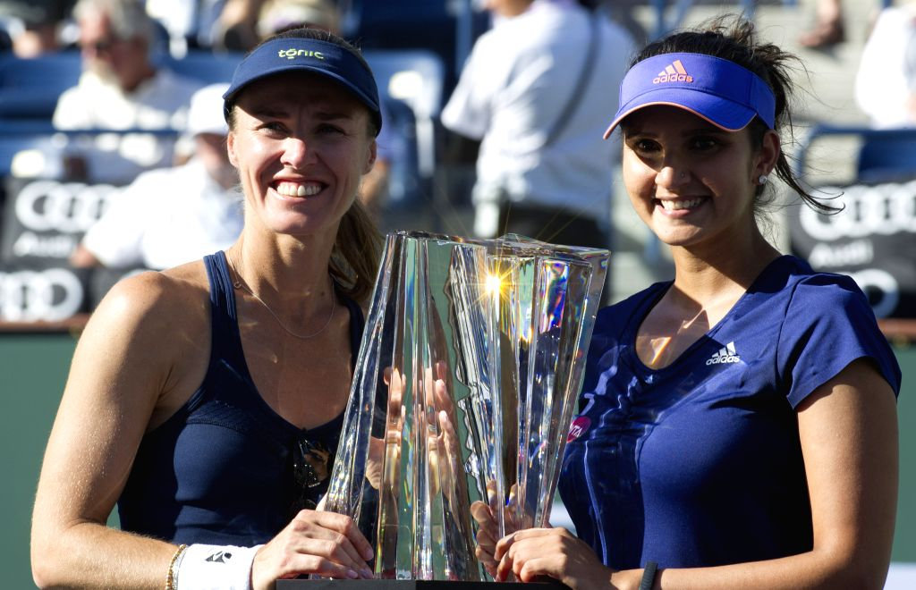 Indian Wells (USA), March 21 Martina Hingis (left) and Sania Mirza with the BNP Paribas Cup trophy at the awards ceremony. Martina Hingis and Sania Mirza won a 2-0 victory over Russia's ...