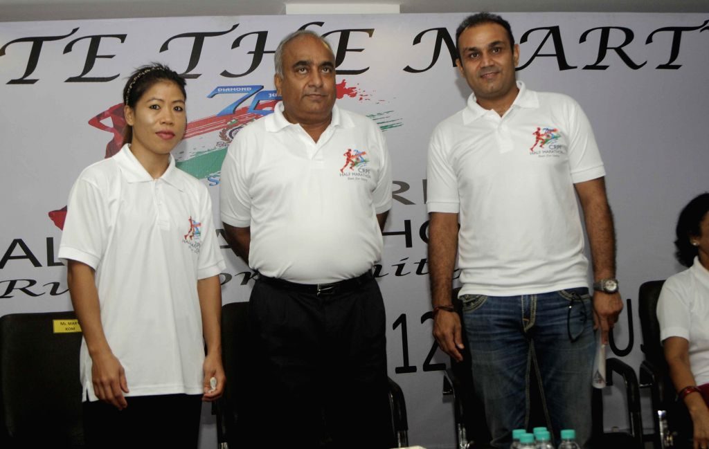 Indian woman boxer Mary Kom and Indian cricketer Virender Sehwag with CRPF DG Dilip Trivedi during a press conference in New Delhi on Aug 12, 2014.