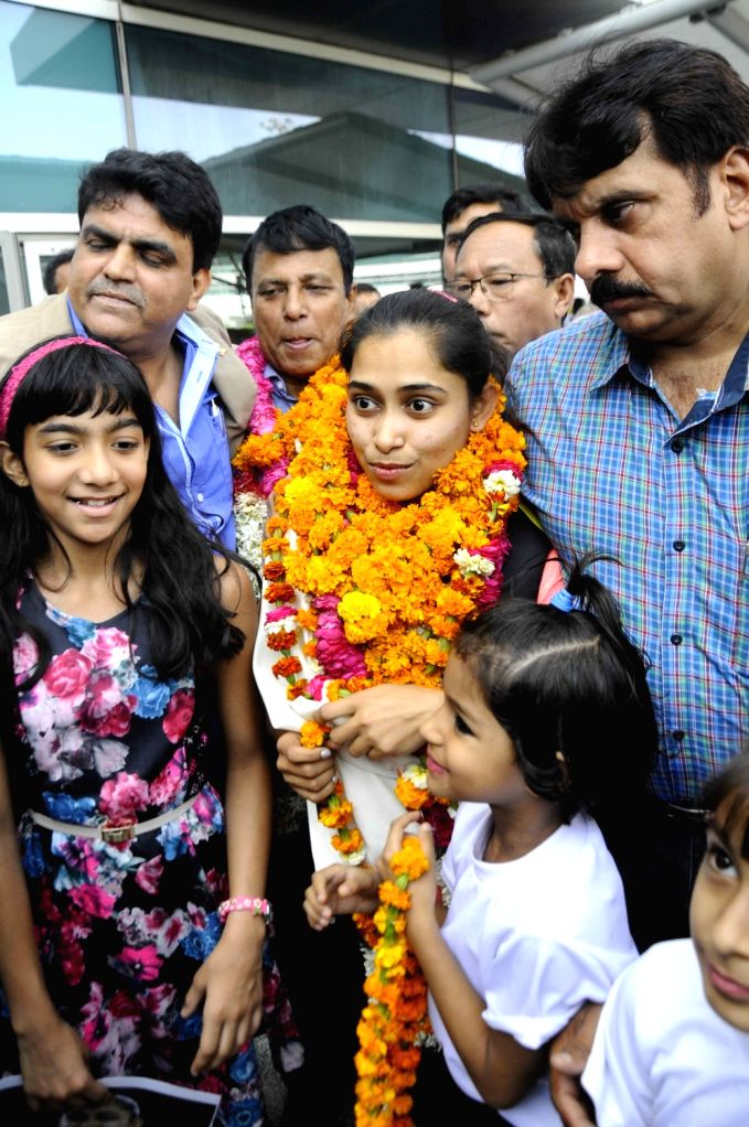 Indian woman gymnast Dipa Karmakar who has created history by becoming the first Indian woman gymnast to qualify for Olympics arrives at Delhi Airport with her coach BS Nandi on ...