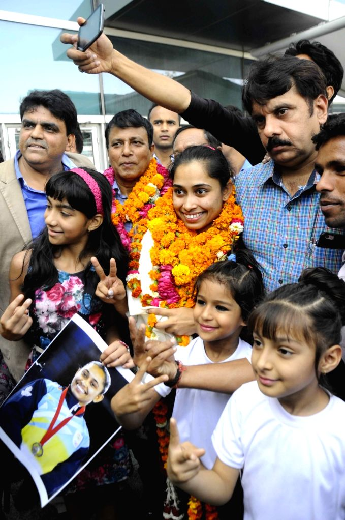 Indian woman gymnast Dipa Karmakar​ who has created history by becoming the first Indian woman gymnast to qualify for Olympics​ arrives ​at Delhi Airport with her coach BS Nandi on ...