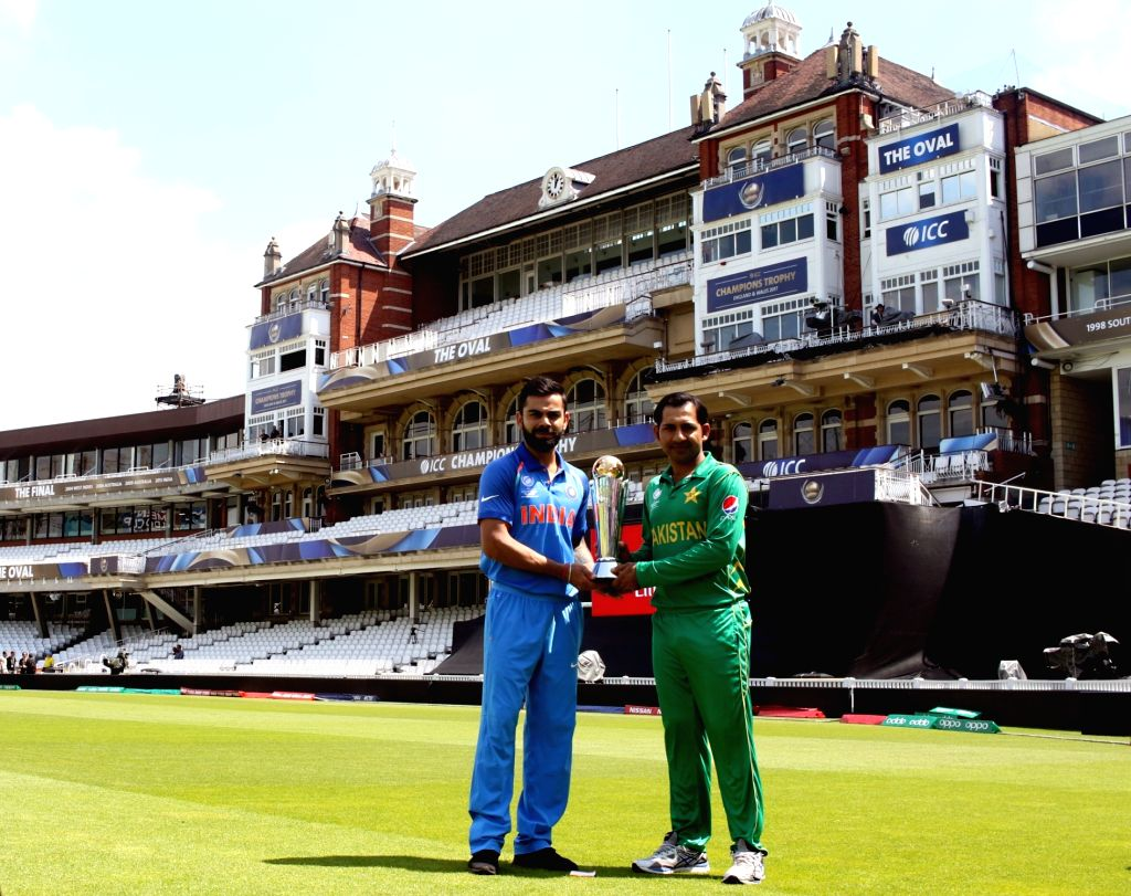 Indias skipper Virat Kohli (R) and Pakistans skipper Sarfraz Ahmed (L) pose with the ICC Champions Trophy on the eve of tournaments final match between India and Pakistan at the Oval in ... - Virat Kohli and Surjeet Yadav