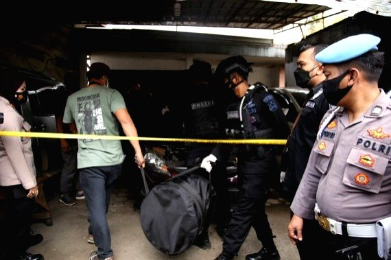 Indonesian police anti-terrorism officers collect evidences from the site where suspected terrorists were arrested in East Jakarta, Indonesia, March 29, 2021.