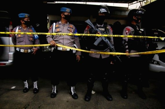 Indonesian police anti-terrorism officers stand guard behind cordon lines at the site where suspected terrorists were arrested in East Jakarta, Indonesia, March 29, 2021.