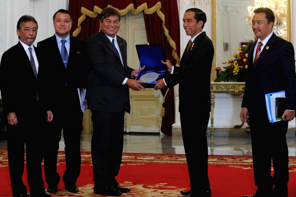 Indonesian President Joko Widodo (2nd, R) receives a souvenir from a delegate of the Federation of International Football Associations (FIFA) at the Presidential ...