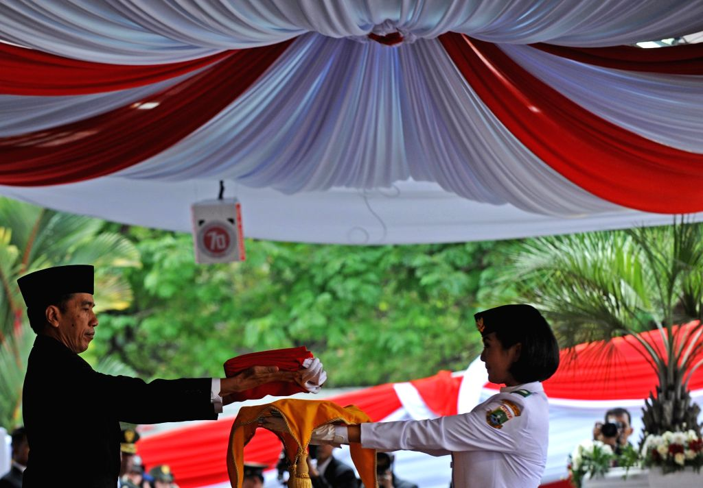 Indonesian President Joko Widodo (L) hands the Indonesian national flag to a member of flag-raising squads during a celebration marking the 70th anniversary of ...